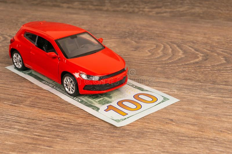 Red car and 100 dollars banknote. Insurance concept royalty free stock image