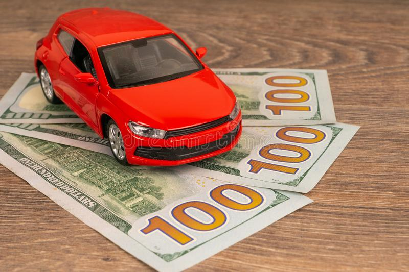 Red car with 100 dollars banknotes, expencive auto service or repair. Red car with 100 dollars banknotes, rich auto service or repair concept stock photography