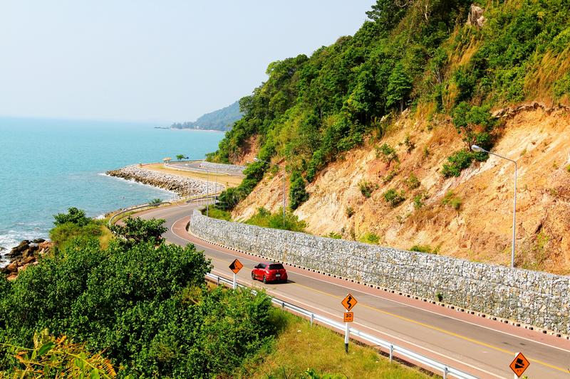 Red car driving on the beautiful curve road beside sea view and mountain on vacation day at Viewpoint Nang Phaya, Chanthaburi, Tha stock photography