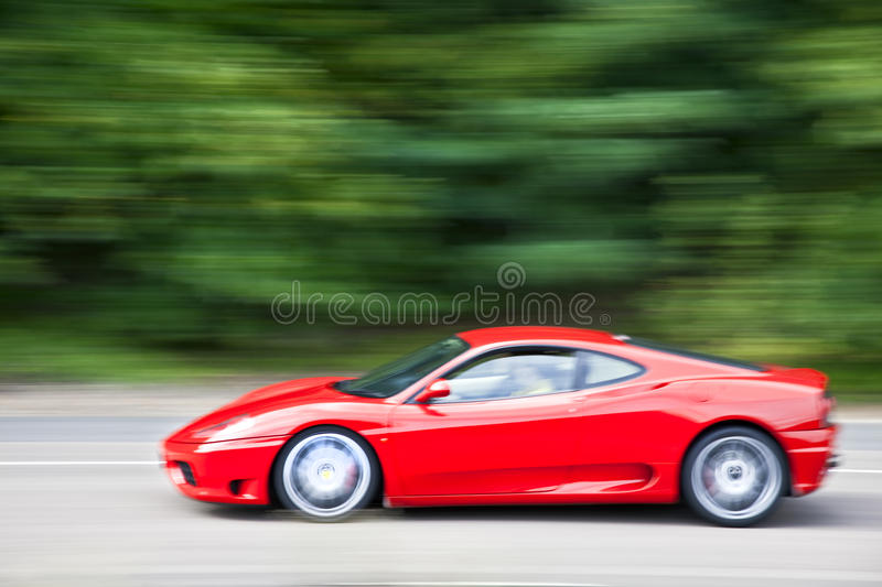 Red car driving fast on country road. A red car driving fast on country road royalty free stock photo