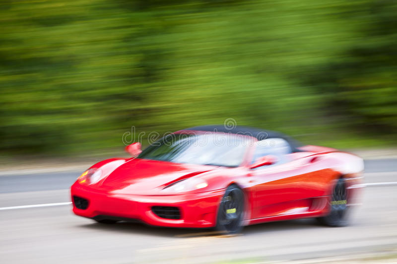 Red car driving fast on country road. A red car driving fast on country road stock image