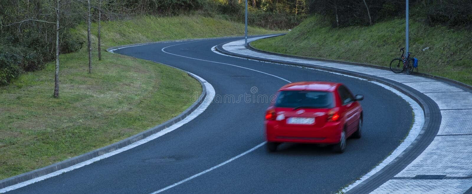 Red car driving fast on the curve of road stock photography