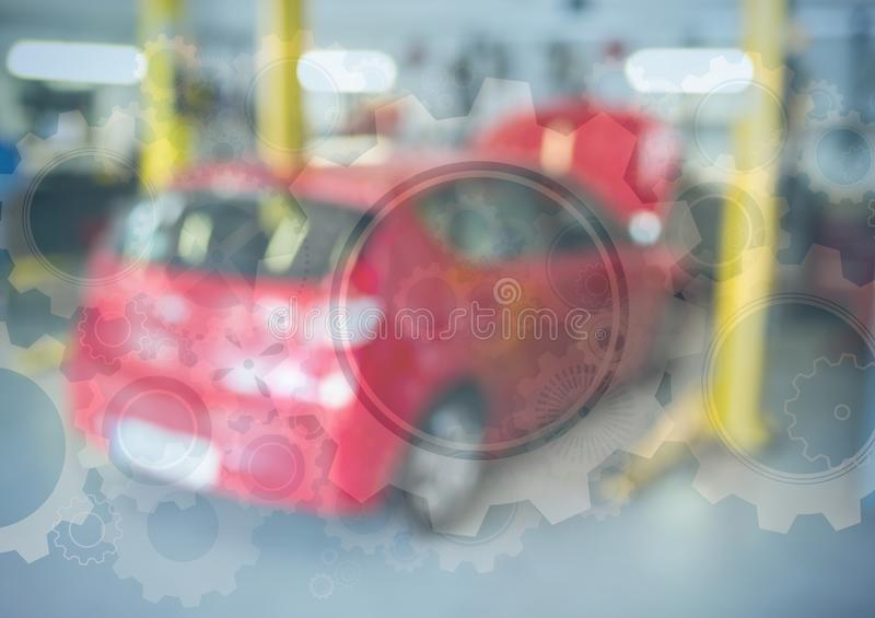 Red car in garage with gear graphic overlay. Digital composite of Red car in garage with gear graphic overlay royalty free stock image