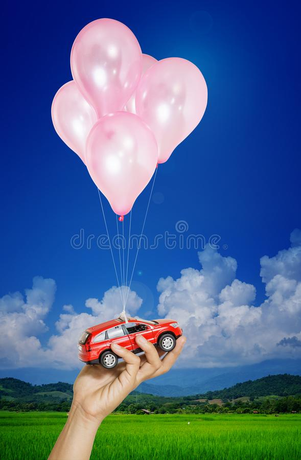 Red car in hand woman hanging on many balloons flying over blue sky. Automobile asset concept. Red car in hand woman hanging on many balloons flying over blue royalty free stock images