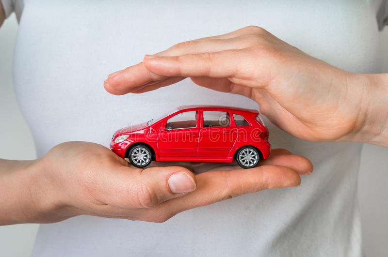 Red car in hands - insurance, rent and buying car concept. Red car in female hands - insurance, rent and buying car concept stock image