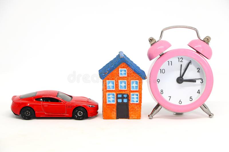 Red car and house model with alarm clock. Red car and house model with alarm clock on white background. concept of buy sell royalty free stock image