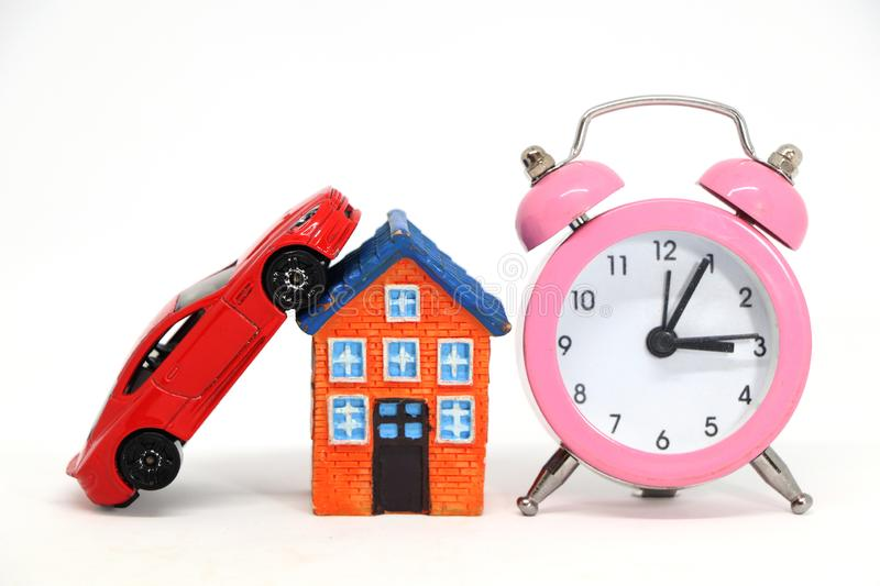 Red car and house model with alarm clock. Red car and house model with alarm clock on white background. concept of buy sell stock images