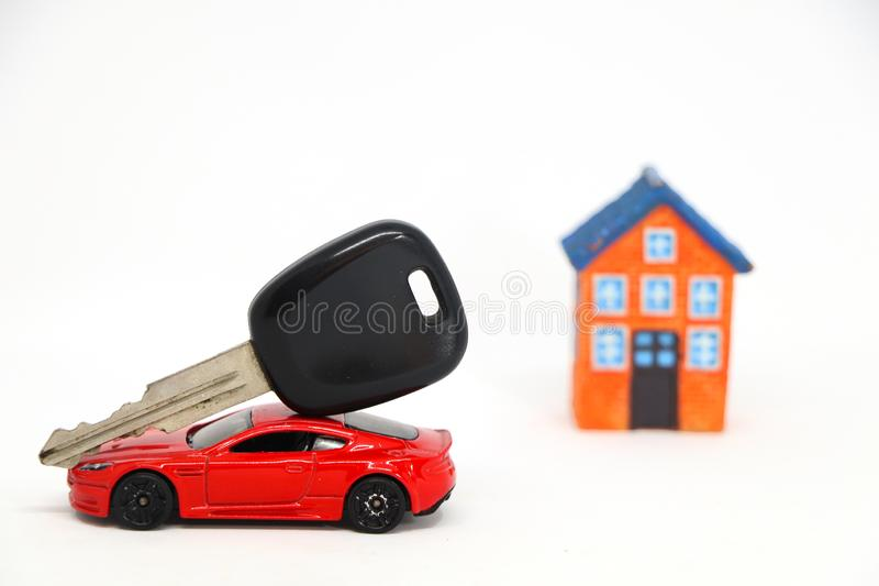 Red car with key with house model in background. Red car with key with house model in background on white. concept of buy sell royalty free stock images
