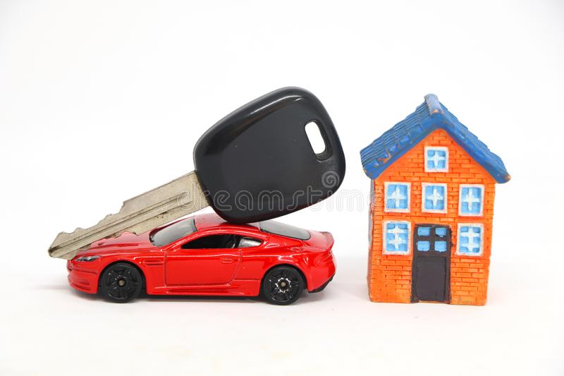 Red car with key with house model. Red car with key with house model on white background. concept of buy sell stock photos