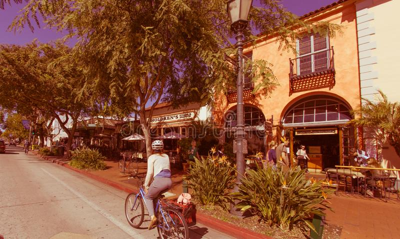 A red car on main shopping street of santa barbara, buildings in. Santa Barbara, United States - February 25 , 2013 : shops in different colors on main streetand stock image