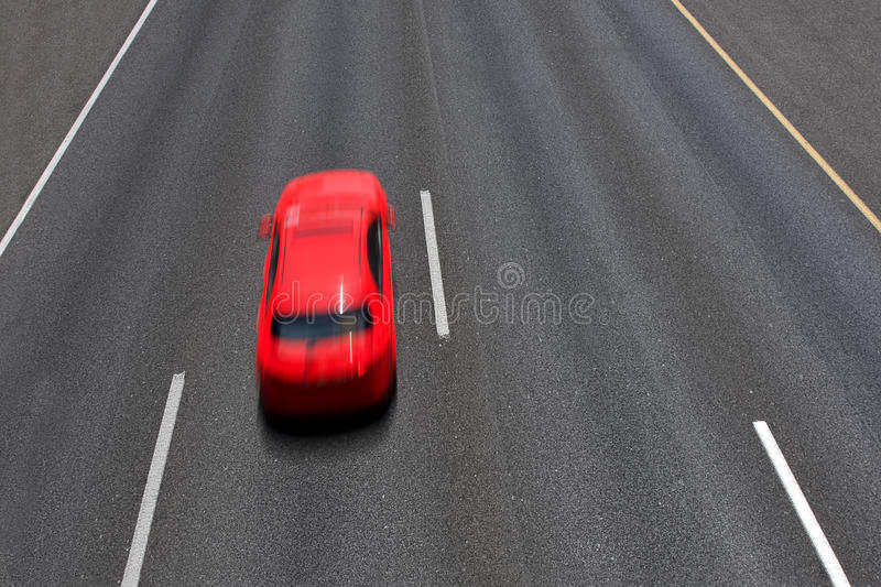 Red car moves fast on highway. Red car moves fast on empty multilane highway ( long exposure, motion blurred, view from above stock image