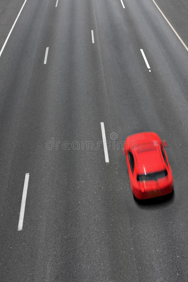 Red car moves fast on highway. Vertical oriented image of red car moves fast on empty multilane highway ( long exposure, motion blurred, view from above stock image