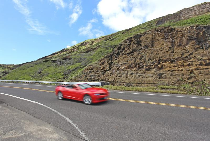 A red car on one of the Hawaiian highways. The red car is rapidly hurtling along a smooth highway. Blue sky and a spectacular Hawaiian landscape are there around royalty free stock photo