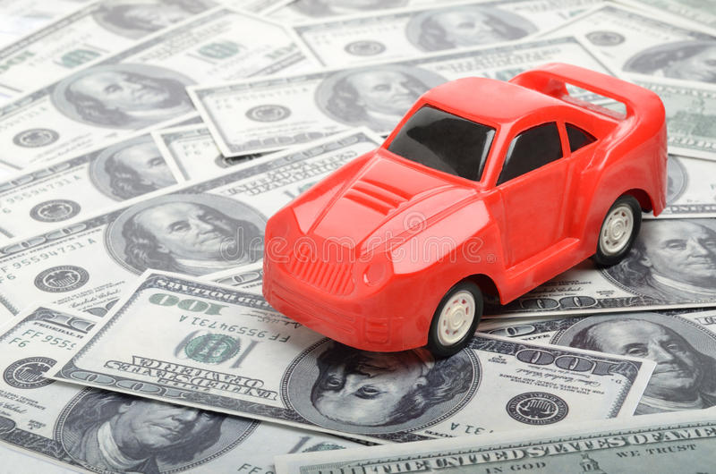 Cost of buying a car. Red car over a lot of dollar bills stock photos