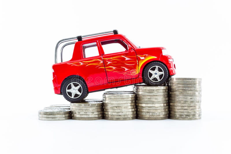 Red car over a lot of stacked coins. Red car over a lot of stacked coins isolated on white background royalty free stock photo