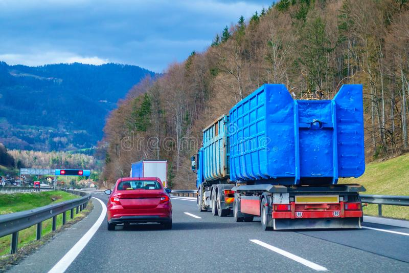 Red car overtaking blue truck on highway stock image