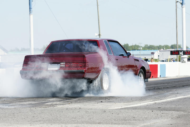 Red car at the races. Red car burns rubber on a quick start -Buick grand national stock image