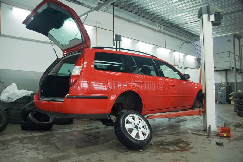 Red car on raiser. Replacing winter tyre for summer tyre at the end of winter season in vulcanization works. Red car lifted on raiser stock photography
