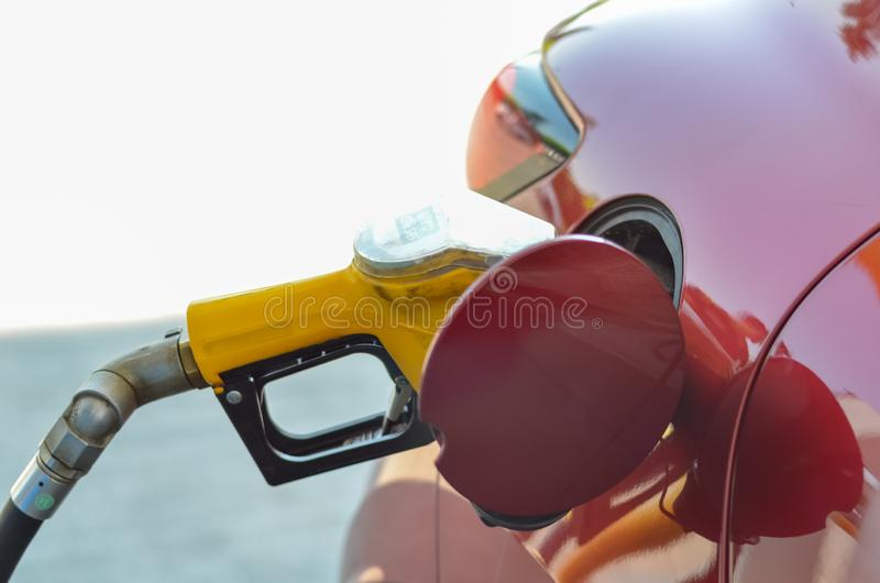 Red car is refueling in filling station stock photography