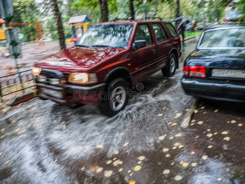 Red car rides in the yard on a wet road in the rain . Beautiful splashes of water from under the wheels. stock photo