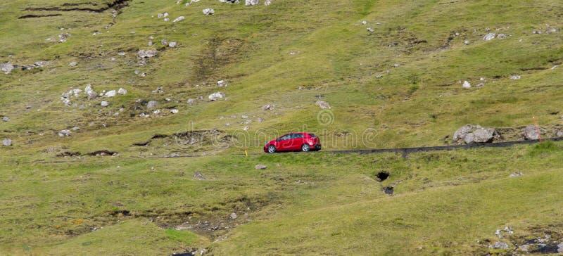 A red car runs through the desolate hills of the faroe islands.  stock photo