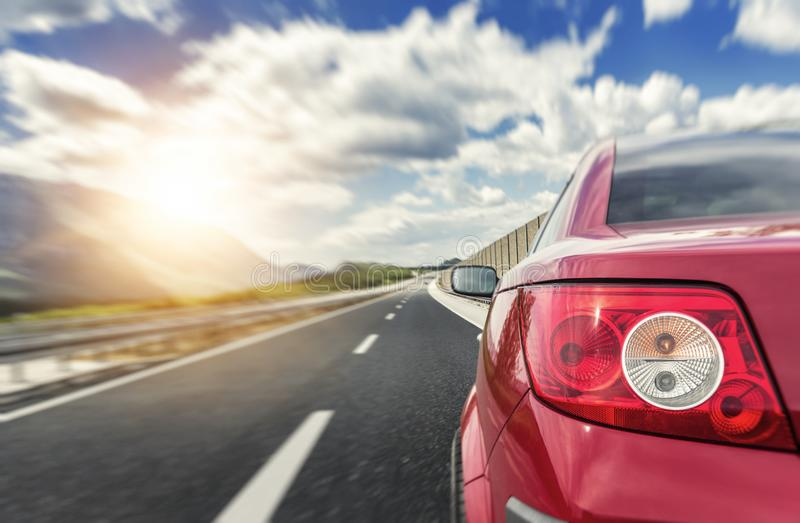 Red car rushing along a high-speed highway. Toned photo stock photos