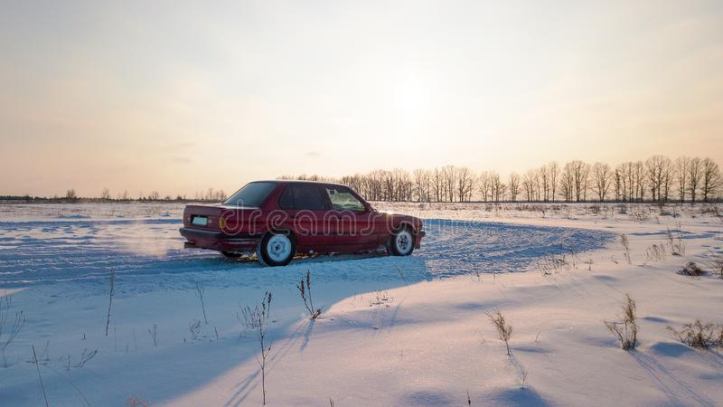A red car is standing on a snowy road during sunset.  royalty free stock images