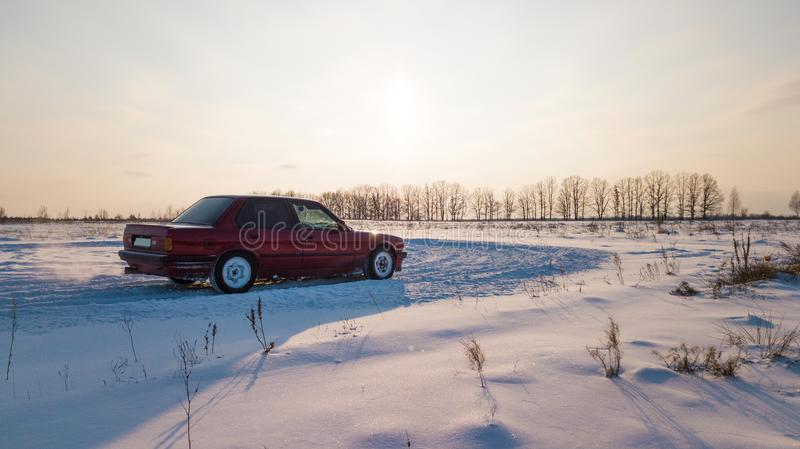 A red car is standing on a snowy road during sunset.  royalty free stock photos