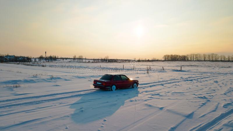 A red car is standing on a snowy road during sunset.  royalty free stock photography