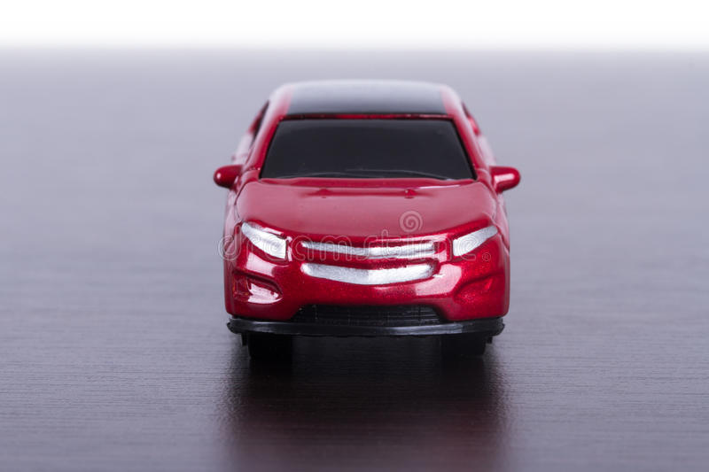 Red Car on Table. Front view of red, toy, small car on wooden table stock photos