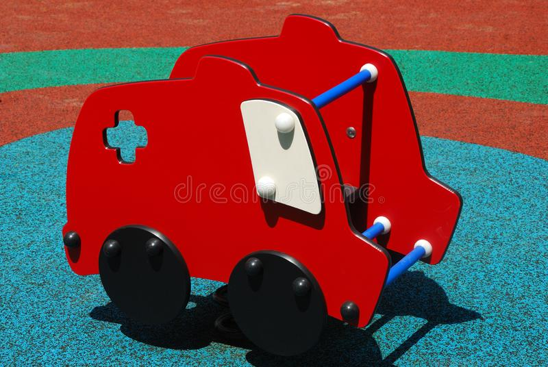 A Red car van ride rocking toy at a playground. A photo taken on a red car van ride rocking toy at a playground stock image