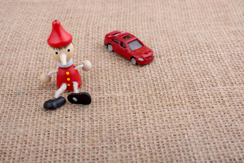 Red car and wooden Pinocchio doll. Sitting on canvas stock image