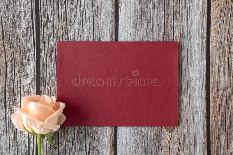 Red card and peach color rose. A piece of bright red paper with a single peach color rose on brown wooden background.   Mock up invitation card. Top view. Flat stock photography