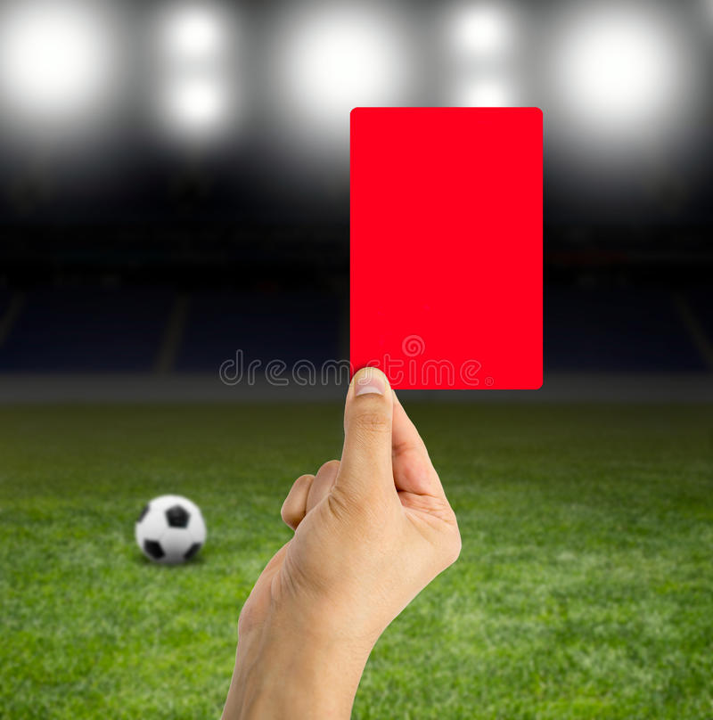 Red card in the spotlight. Football referee showing you the red card in a stadium under the bright focuses royalty free stock photo