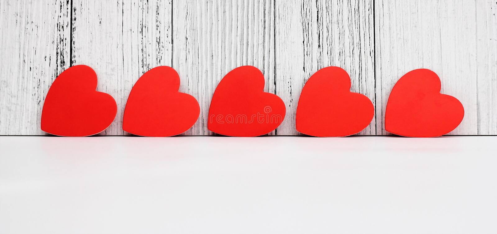 Red cardboard hearts are arranged in a row. Design and decoration for Valentine`s Day. concept of love. Copy Space royalty free stock photos
