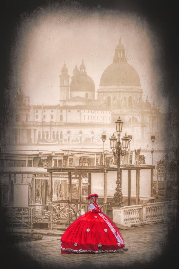 Red carnival mask against Basilica Santa Maria della Salute in Venice, Italy. Carnival mask against Basilica Santa Maria della Salute in Venice, Italy stock photo