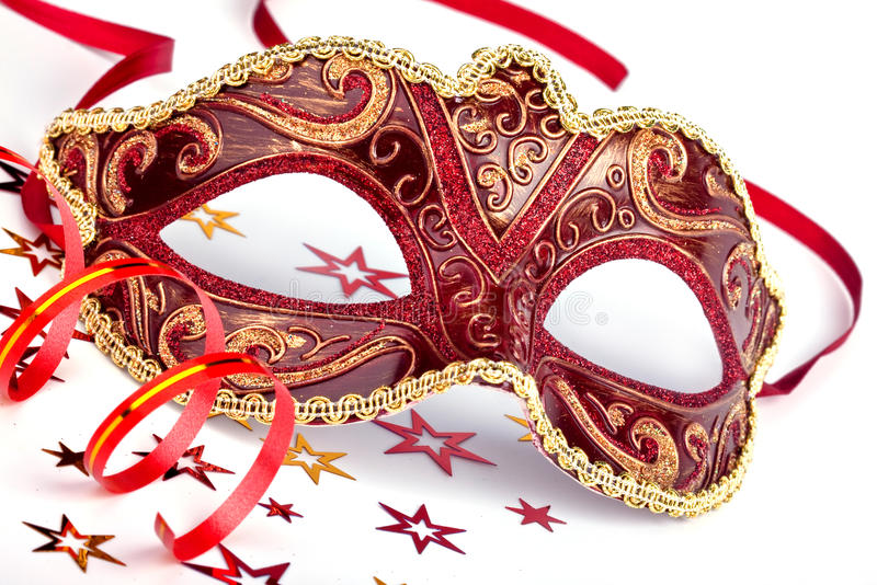 Red carnival mask with confetti and streamer. Red masquerade mask with confetti and streamer stock photo