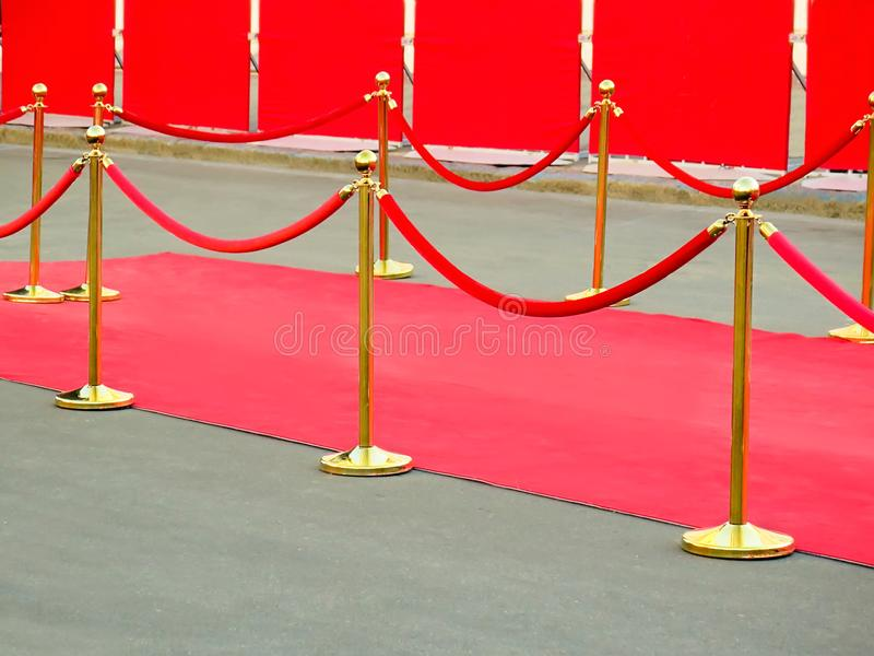 Red carpet entrance with golden stanchions and ropes. Celebrity nominees to premiere. Stars on the festive awarding of prizes. Awards royalty free stock photography
