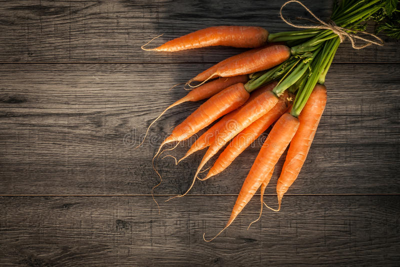 Red carrot on wooden background table. stock photos