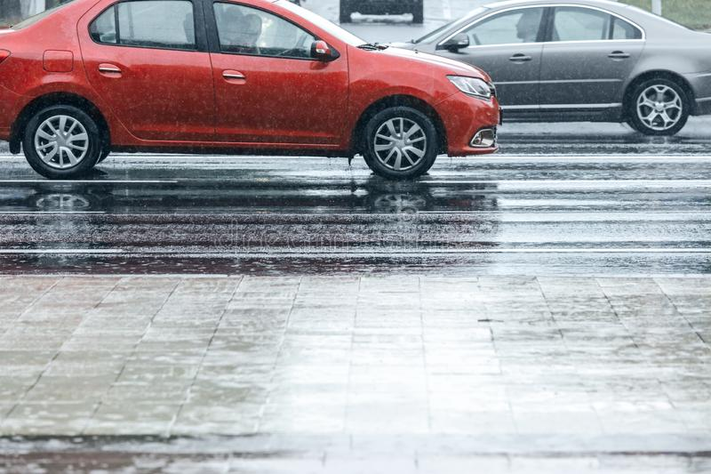 Red cars driving on wet asphalt road during rainy weather. Red cars driving on wet asphalt city road during rainy weather stock photography