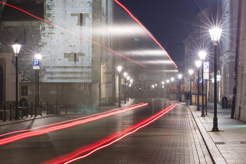 Red cars trails on the night street in Krakow stock photography
