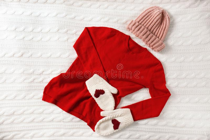 Red cashmere sweater, hat and mittens on knitted plaid royalty free stock photo