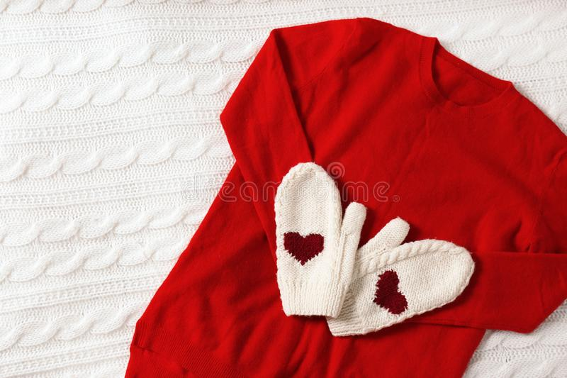 Red cashmere sweater and mittens on knitted plaid stock image