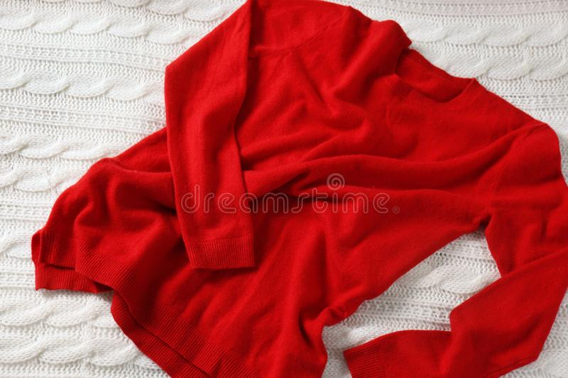 Red cashmere sweater. On white knitted plaid stock images