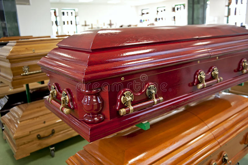 Red casket. Close up of the red wooden casket displayed in a casket store royalty free stock photography
