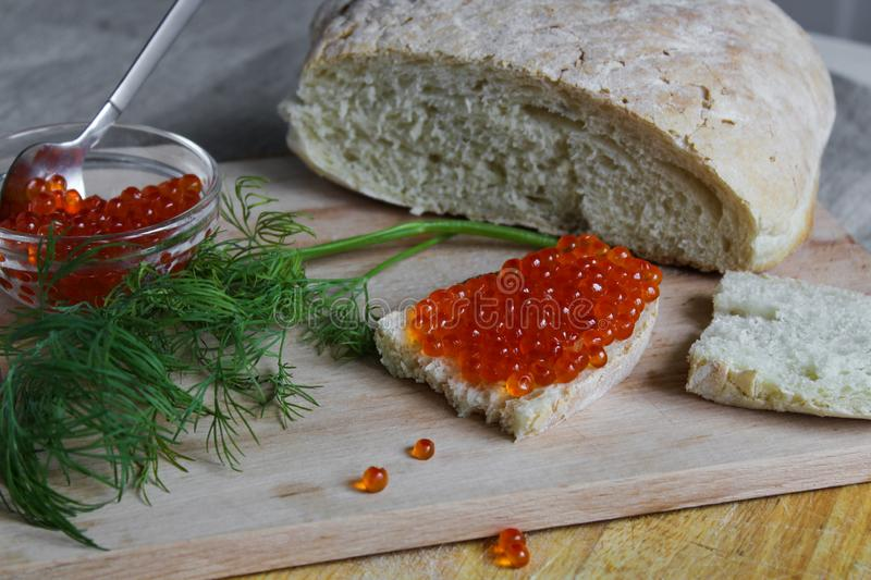 Red caviar in bowl and fresh bread with a sandwich on a wooden board on a gray background royalty free stock image
