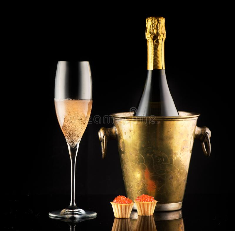 Red caviar and champagne in a bottle and a glass. On a black background stock photos