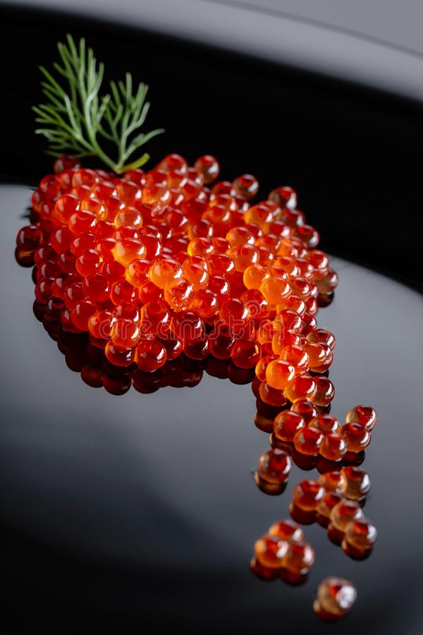 Red caviar with dill. On a black plate. Selective focus royalty free stock images