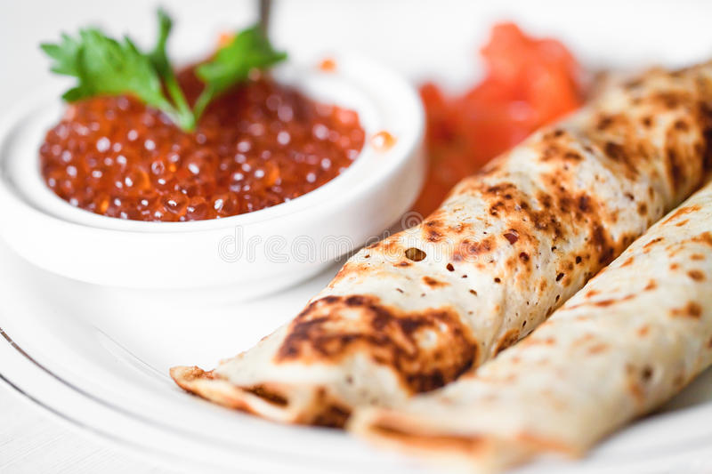 Red caviar with pancakes. On plate royalty free stock photography
