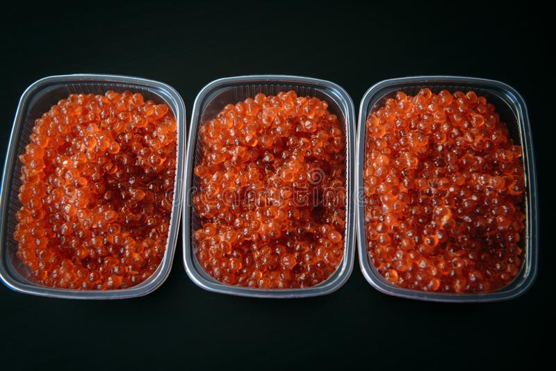 Red caviar in plastic containers close up, top view, black background. Gourmet food royalty free stock image